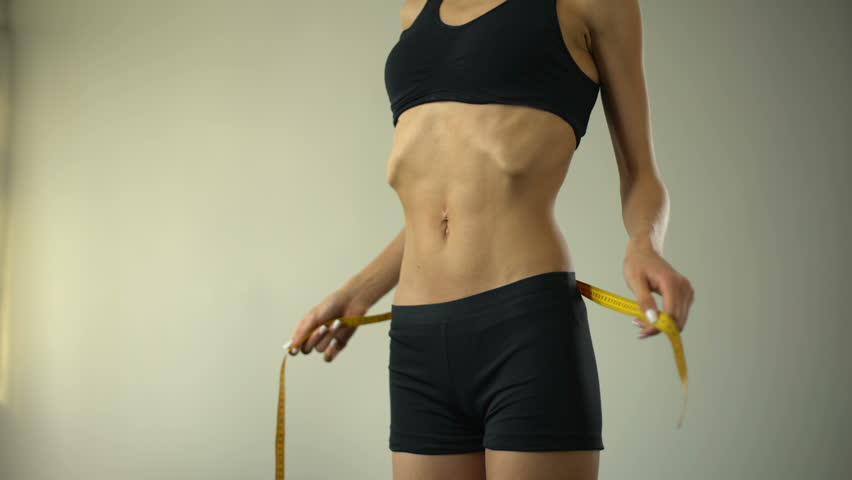 Slim girl measuring waist with tape-line, showing ok, anorexia as mental illness