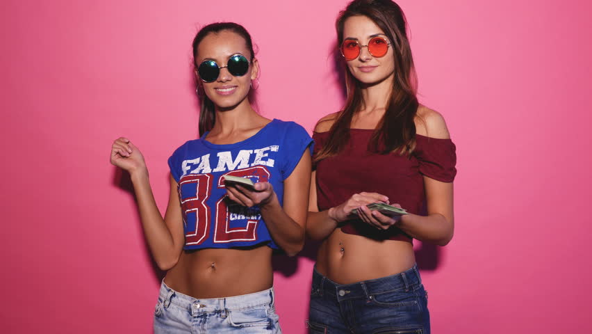 Two young sexy stylish smiling brunette women making it rain money. Hot girls dressed in summer hipster clothes and throwing bills out of a bundle money. Posing on pink background. 4k | Shutterstock HD Video #1017853591