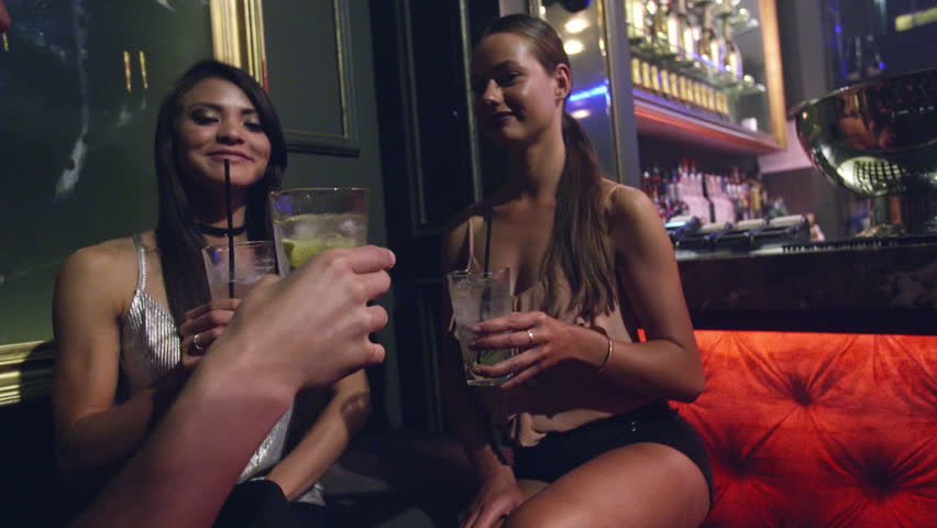 Young man and women laughing with making a toast of cocktails and have good time in nightclub party. Group of friends enjoying drinks at nightclub. | Shutterstock HD Video #1017853753