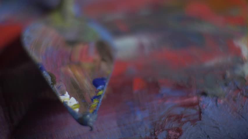 The artist's palette knife lies on the palette. Clous-up. The master of the artist lies on the palette. 4K