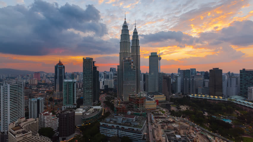 Time lapse: Aerial cityscape view during dusk overlooking the Kuala Lumpur city center skyline and construction area at sunset in Malaysia. Day to night. High Quality 4K