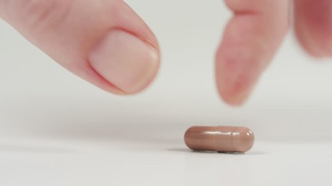 Close up view of a hand taking a brown capsule.