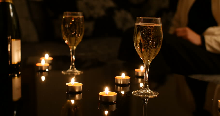 Full glasses of Champagne on black glossy table with red burning candles and champagne bottle, women sitting on sofa in background. Cosy romantic Christmas vacation atmosphere  | Shutterstock HD Video #1017879676
