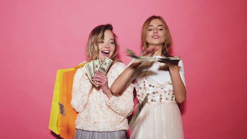 Two young stylish smiling blond women holding shopping bags and making rain money. Hot girls dressed in summer hipster clothes and throwing bills out of a bundle money. Posing on pink background | Shutterstock HD Video #1017887587