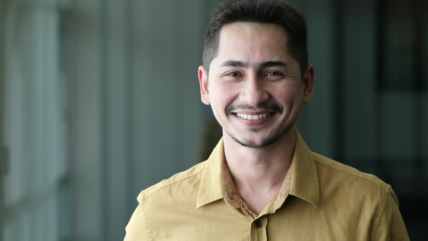 Young man asian smiling and looking at camera. Portrait of a happy handsome young man in office. Close up face of young cool trendy man looking at camera | Shutterstock HD Video #1017895762