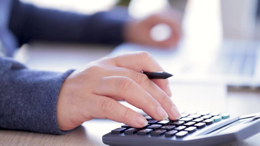 Close up shoot of a female hand doing some calculations and taking notes