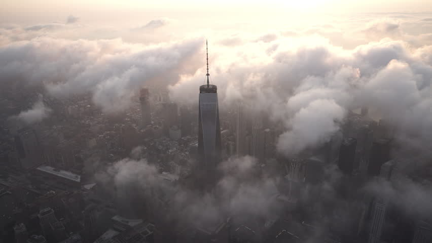 New York City Circa-2015, aerial view orbiting Lower Manhattan's Financial District and the World Trade Center with fog and low level clouds at sunrise