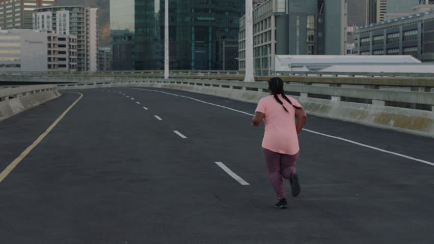 Overweight woman running resting exhausted after difficult cardio exercise tired black female in urban city at sunrise | Shutterstock HD Video #1017906676