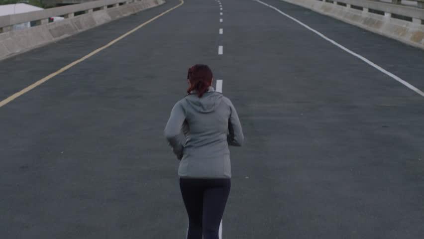 Woman runner jogging on city street exercising enjoying casual run at sunrise rear view | Shutterstock HD Video #1017906712