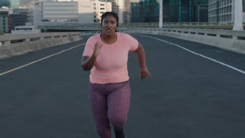 Young overweight black woman running resting exhausted after difficult running cardio exercise tired african american female in urban city at sunrise | Shutterstock HD Video #1017906715