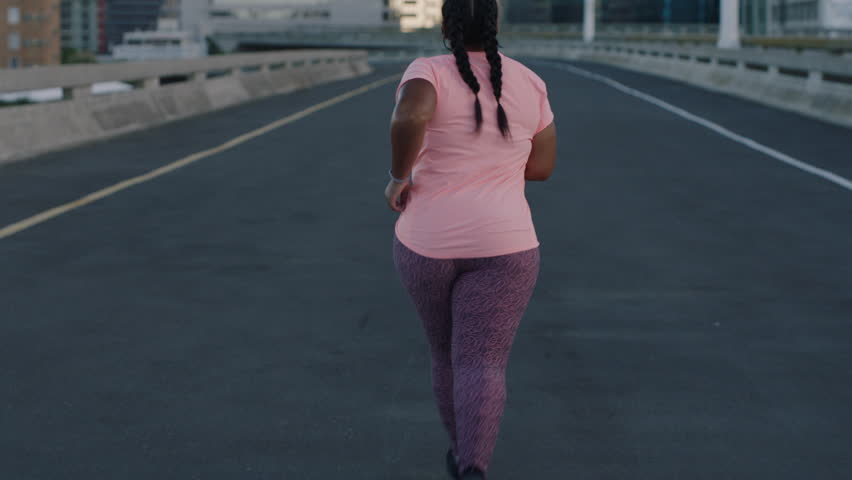 Overweight woman athlete runner exercising running weight loss workout jogging in urban city background at sunrise rear view | Shutterstock HD Video #1017906730