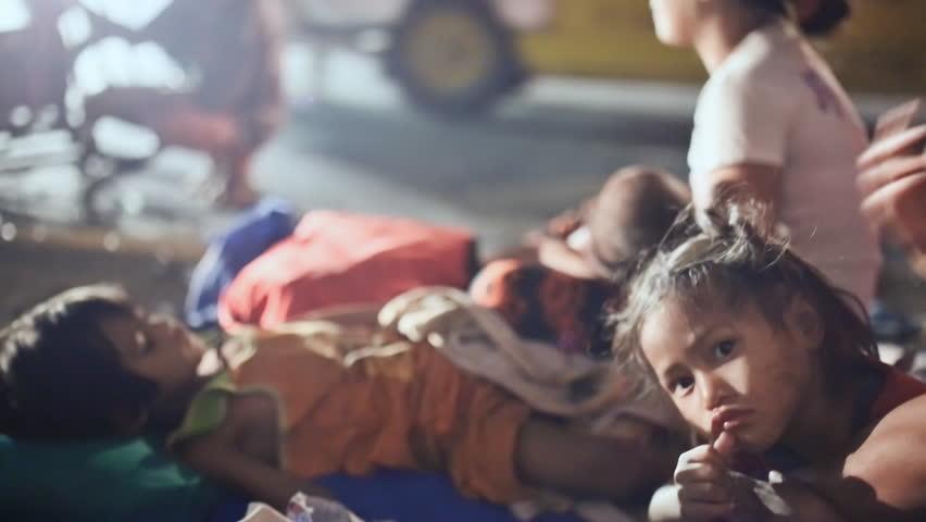 MANILA, PHILIPPINES - JANUARY 5, 2018: A homeless, poor Filipino family sleeping on the street near the road. Manila.