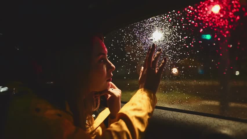 Young Woman Looking Out of the Moving Car Window at Night. SLOW MOTION. Girl sitting on the back passenger seat of driving car. Night City Traffic on background.
