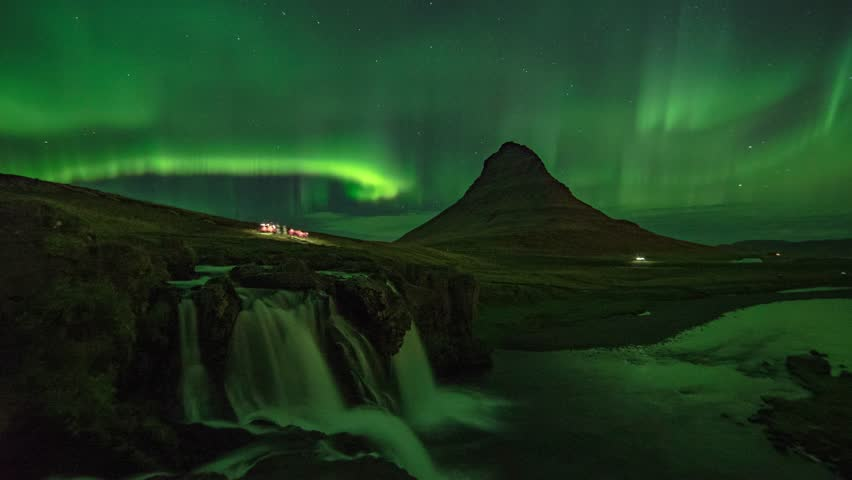 Scenic Time Lapse view of Aurora Borealis (Northern Lights) at Kirkjufellsfoss, in Iceland. Famous travel destinations.
