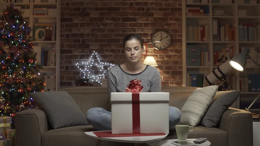 Disappointed woman receiving a bad Christmas gift at home, she opens the box and finds a pair of ugly slippers   Shutterstock HD Video #1017930184