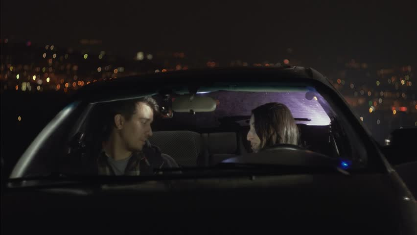Young couple in love in car kissing on the background of night lights