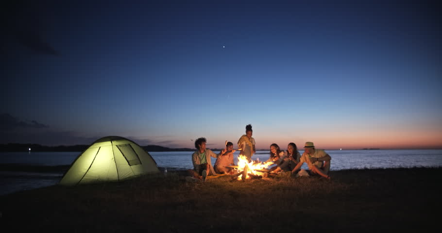 Group of six old multi-ethnic friends sitting near bonfire, roasting sausages, having a summer beach party, talking, enjoying their time 4k | Shutterstock HD Video #1017949582
