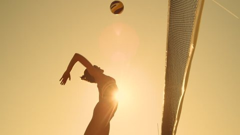 SLOW MOTION, LOW ANGLE, CLOSE UP, SUN FLARE: Athletic girl playing beach volleyball jumps in the air and strikes the ball over the net on a beautiful summer evening. Caucasian woman score a point.
