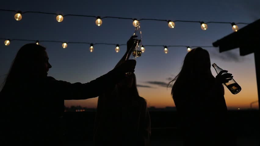 Silhouettes of young people toasting with bottles and dancing with raised arms to the music played by dj at rooftop party during beautiful city sunset | Shutterstock HD Video #1017958993