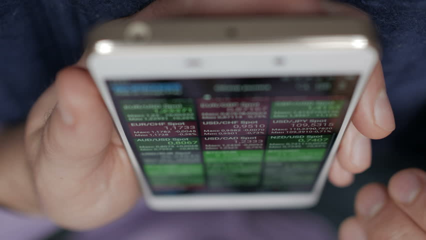 Businessman reading financial news. Stock market, trading online, trader working with smartphone on stockmarket trading floor.  | Shutterstock HD Video #1017960775
