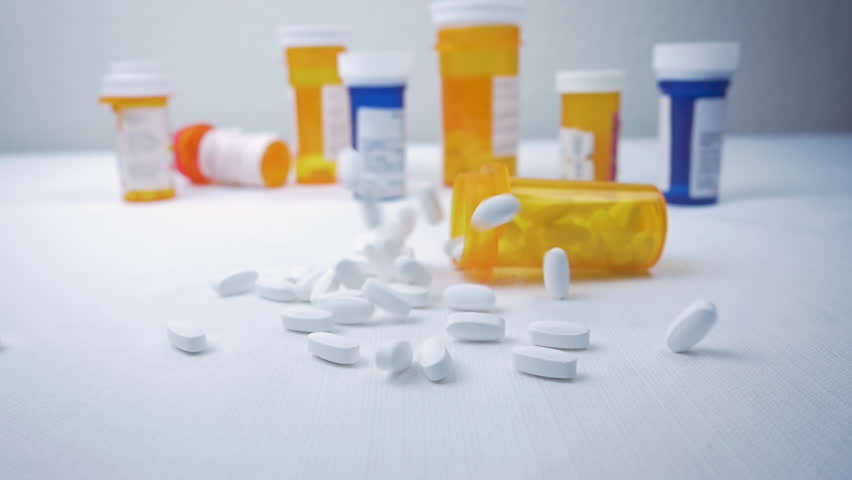 Prescription pill bottle falls on a pile of narcotics in slow motion. Pharmaceutical bottles sit in the background. The painkillers represent the opioid crisis in America, addiction and overdoses. Royalty-Free Stock Footage #1017973762