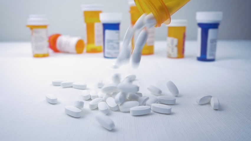 Prescription pills fall into a pile from a bottle in slow motion. Pharmaceutical bottles sit in the background. Painkillers represent the opioid crisis in America, narcotic addiction and overdoses. Royalty-Free Stock Footage #1017973765