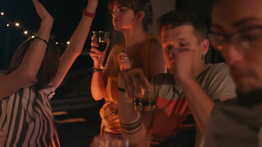 Caucasian group of stylish hipsters holding glasses with red wine in hands and dancing. Young gorgeous people enjoying favorite music. Outdoors. Lifestyle. #1017979024