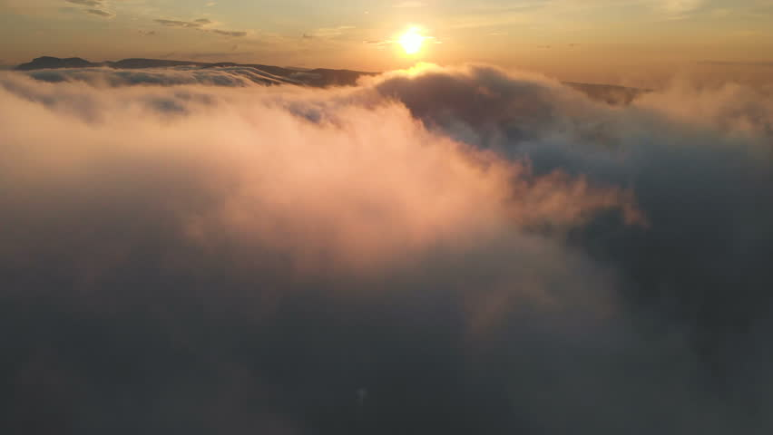 Flying through the clouds at dusk or dawn. Flying in pink clouds in the sun. Aerial view. North Caucasus | Shutterstock HD Video #1017995602