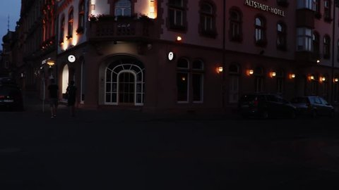 Trier, Germany - 07 15 2018: A car turns into a street with a restaurant and a hotel. Two pedestrians appear the the video.