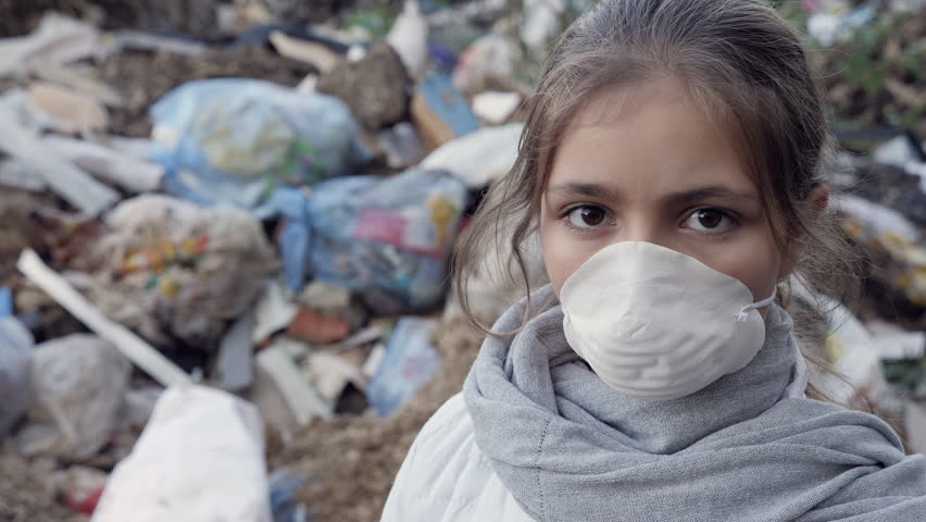 Young girl in a white respirator at the garbage dump looks into the camera. Ecology concept. Slow motion video