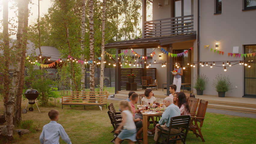Big Family Garden Party Celebration, Gathered Together at the Table Family, Friends and Children. People are Drinking, Passing Dishes, Joking and Having Fun. Panoramic Camera Shot. | Shutterstock HD Video #1018016164