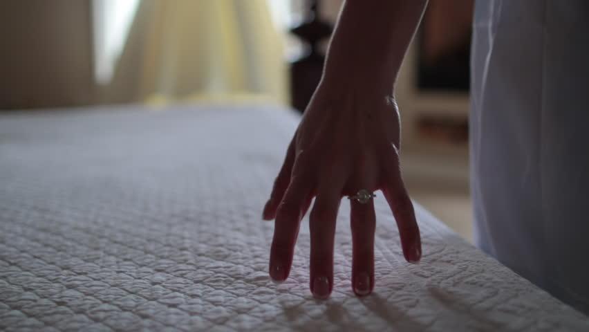 Close up of hand caressing bed towards dress