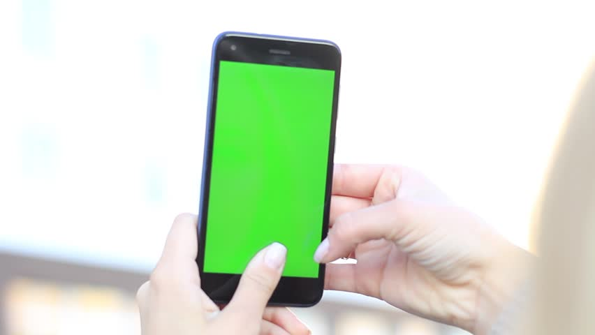 Girl's hands holding a mobile phone with a green screen. | Shutterstock HD Video #1018031608