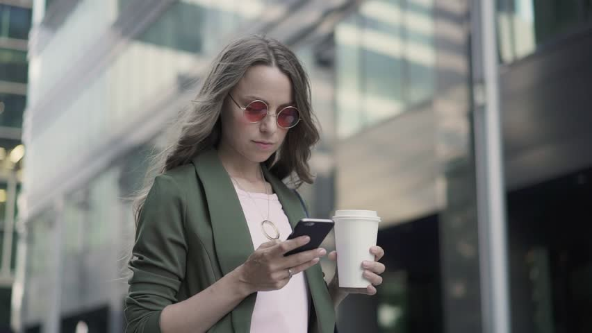 Young girl in khaki jacket is standing in city street, web surfing and drinking coffee to go. Blurred background. Slider slow motion medium shot | Shutterstock HD Video #1018034251