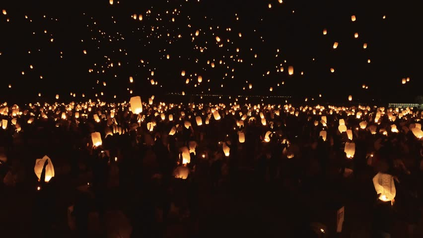 Drone footage of thousands of glowing lanterns flying across screen. Beautiful floating lanterns light the night sky as thousands of people gather to let their wishes fly.