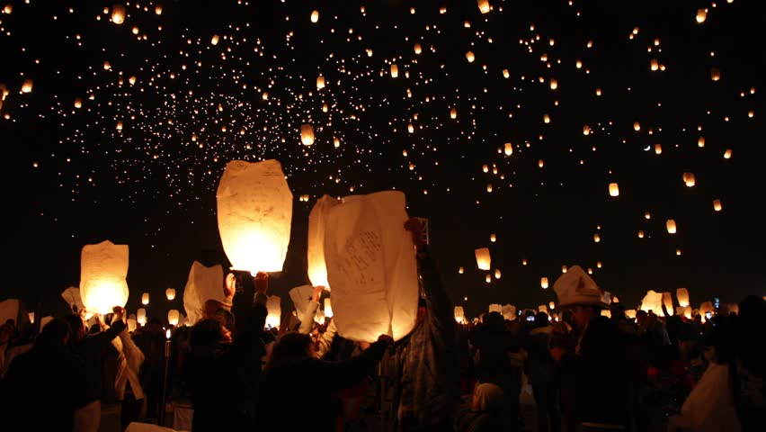 Thousands of lanterns float in the night sky in slow motion. Huge gathering of people light lanterns with flames.