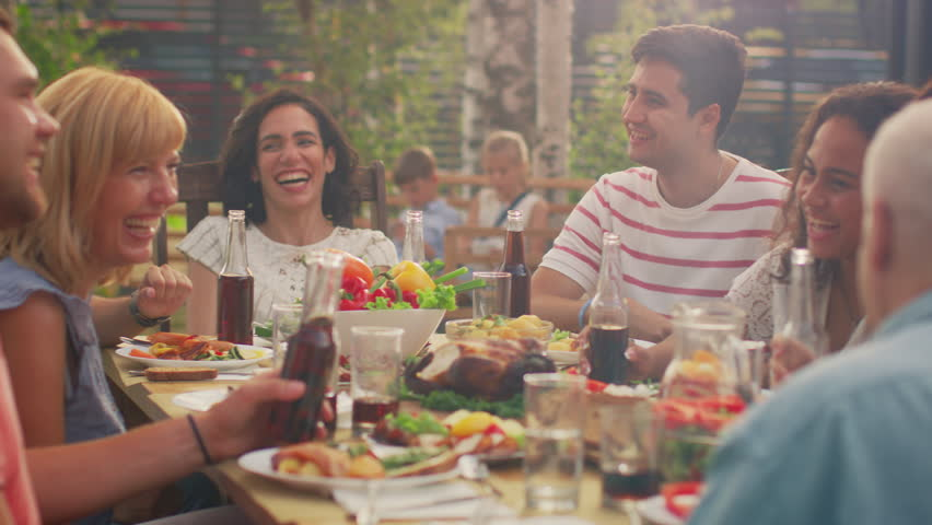 Big Family Garden Party Celebration, Gathered Together at the Table Relatives and Friends, Young and Elderly are Eating, Drinking, Passing Dishes, Joking and Having Fun. | Shutterstock HD Video #1018050766