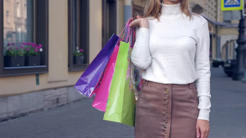 Woman shopping concept. Color paper bags in female hand on street | Shutterstock HD Video #1018051534