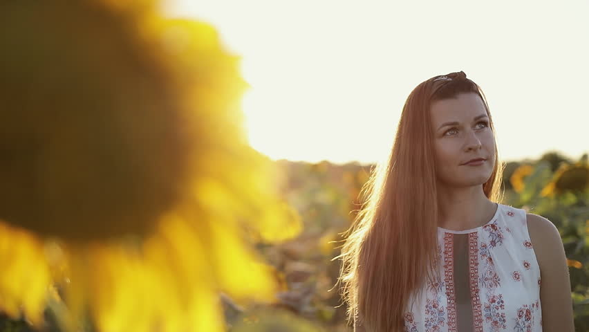 An attractive woman with long hair is standing in a field with yellow sunflowers and looking around. Light flare, lens glare. Slow motion.    Shutterstock HD Video #1018071127