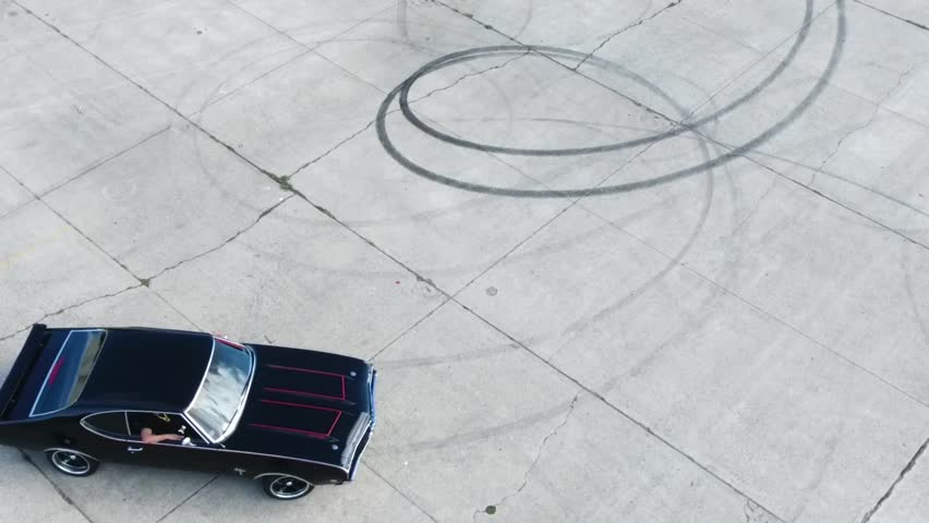 Shot with a a Phantom 4 Professional drone. An aerial shot of muscle car doing donuts in a San Francisco parking lot.