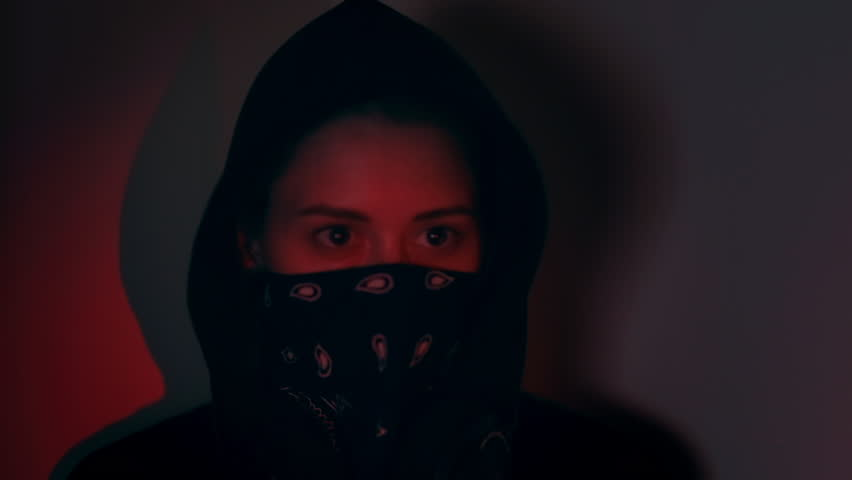 Here you have a shot of a hacker pulling up his/her bandana, getting ready to go into hacker mode. Then proceeds to start hacking, reading and writing code, eyes shifting from side to side. | Shutterstock HD Video #1018100233