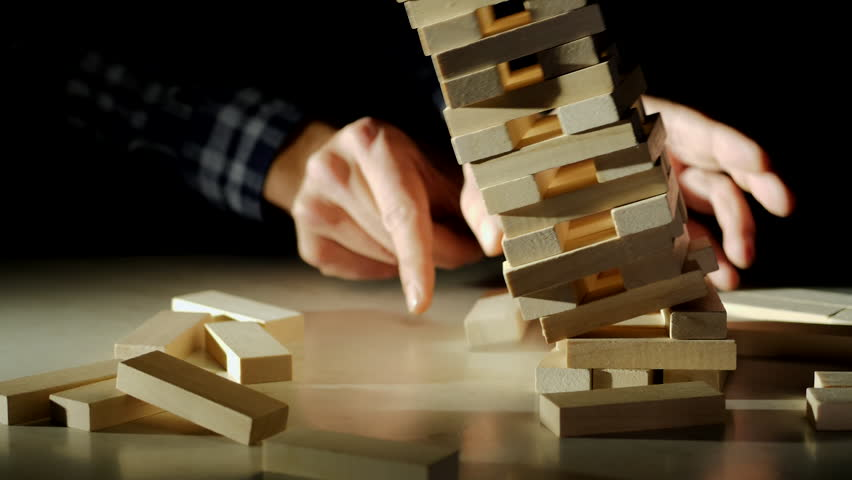 Business risks in the business. Jenga falls on the table, the tower falls. Slow motion video. Male hand pulls out a wooden brick and construction collapses