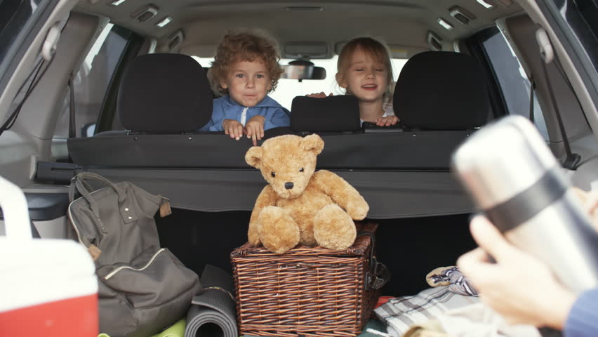 Medium shot of cute little boy with curly hair and cheerful girl sitting in backseat of family car and talking to parents putting picnic essentials in trunk before going on trip