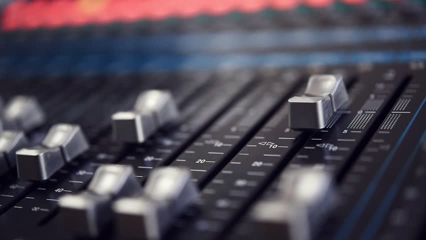 The DJ is adjusting the volume of the sound. Professional audio mixing console