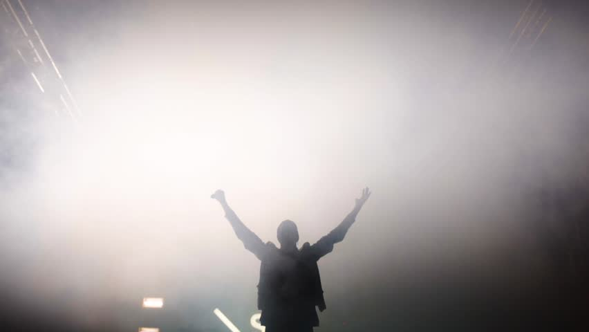 The silhouette of an artist in the stage lights. An artist is rocking on the stage #1018119256