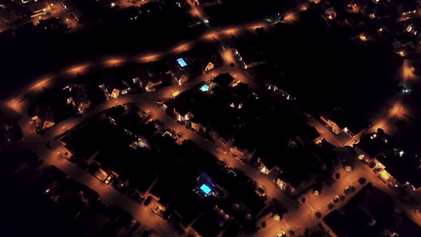 Flyover aerial of a nice suburban area at night, with glowing blue and green swimming pools. | Shutterstock HD Video #1018121890