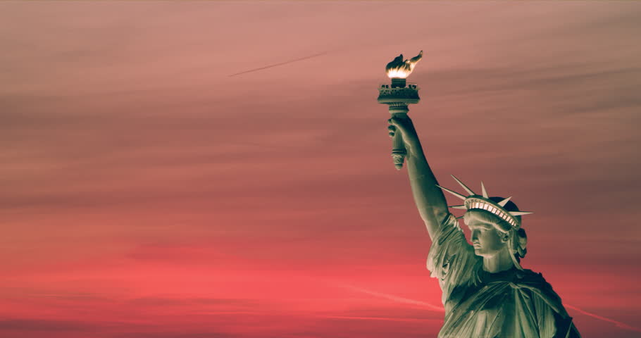 Aerial view of the Statue of Liberty at sunset, New York City, bright summer light. Medium to wide shot on 4k RED camera on helicopter.