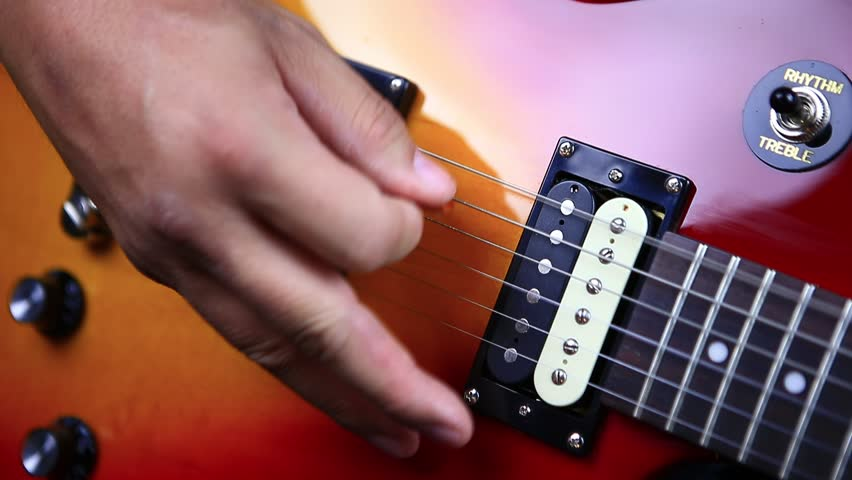 Man picking notes on electric guitar in repeating sequence - rolling arpeggio close up | Shutterstock HD Video #1018125853
