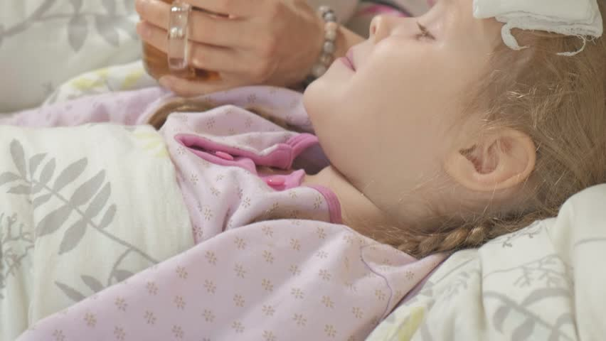 Sick girl with fever. Child with fever: a woman caring for a child and medicating 4k   Shutterstock HD Video #1018138486