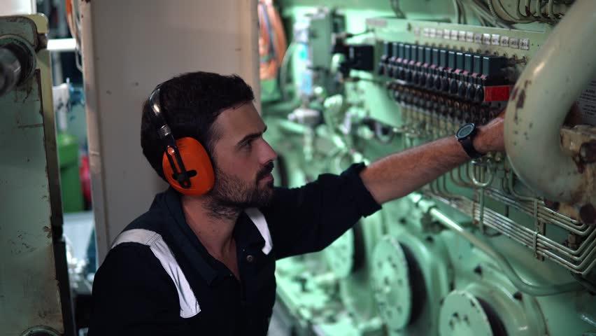 Marine engineer inspecting ship's engine in engine control room ECR. Seamen's work.